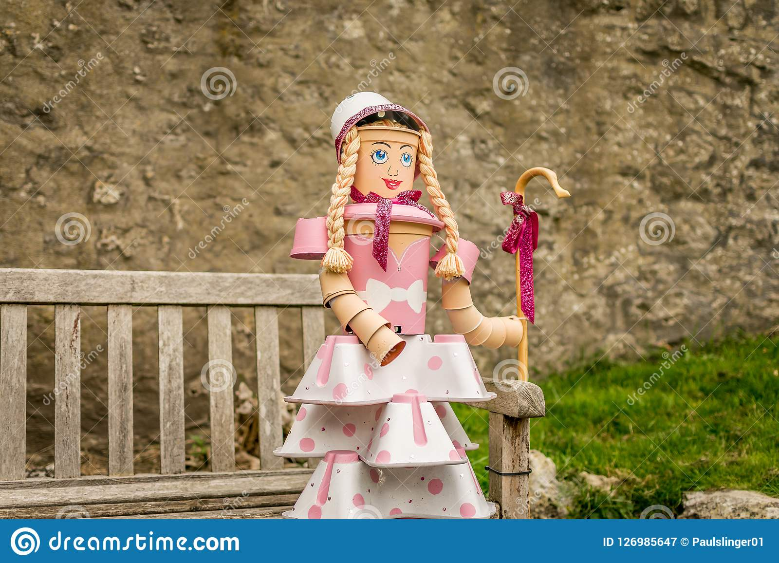 A shepherdess sat on a bench made from plant pots.