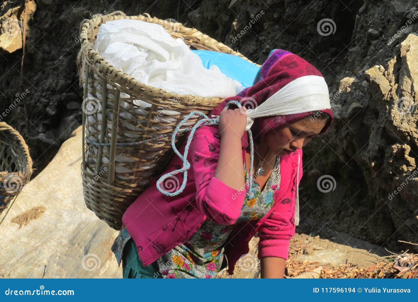 Sherpa furtianu kobieta niesie ciężkiego ładownego kosz w Nepal