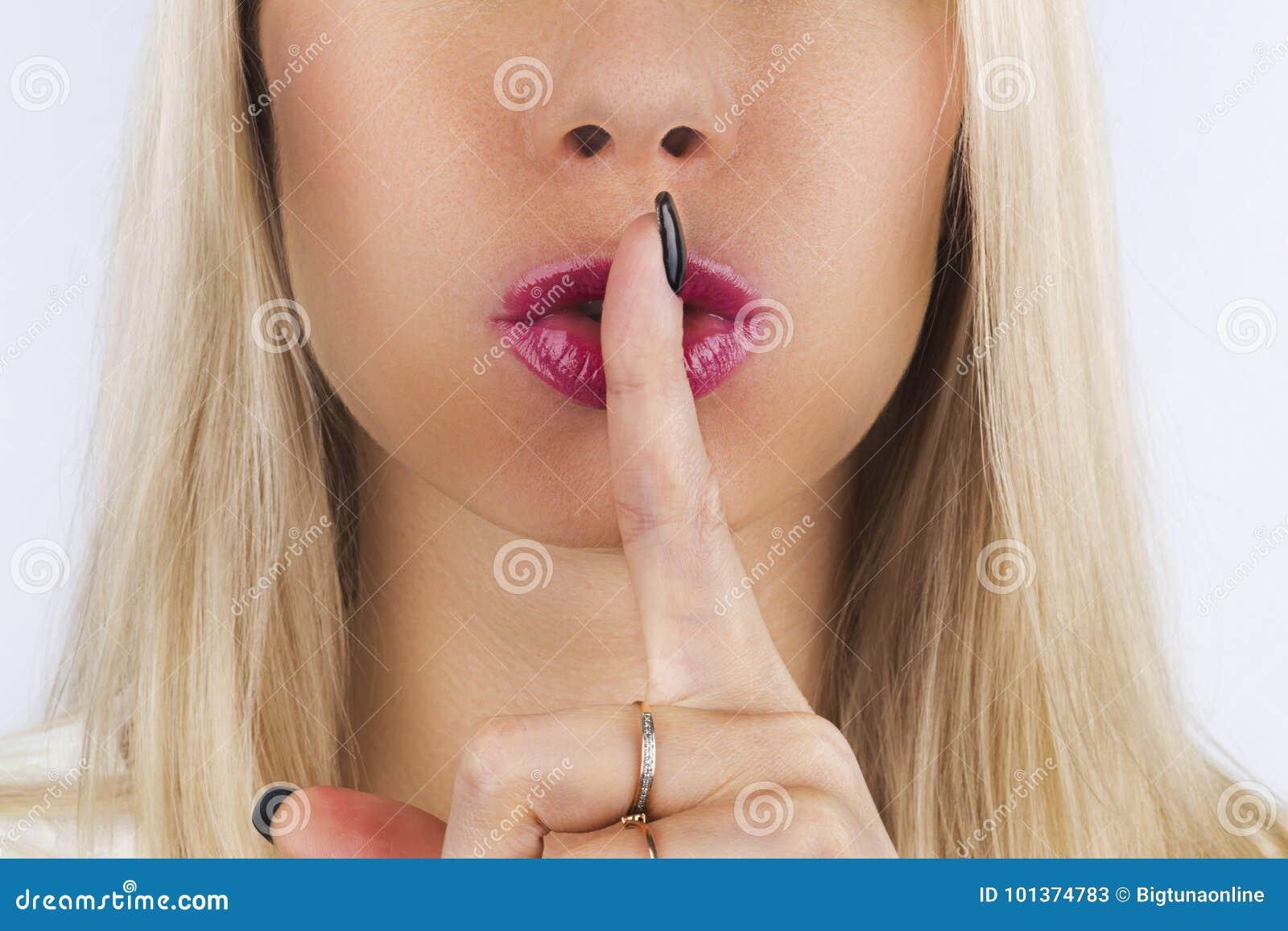 Shh! Frauen ` s Geheimnisse Schöne blonde Frau, die ihren Finger zu ihren rosa Lippen in einer Geste für Ruhe hält Herstellung de