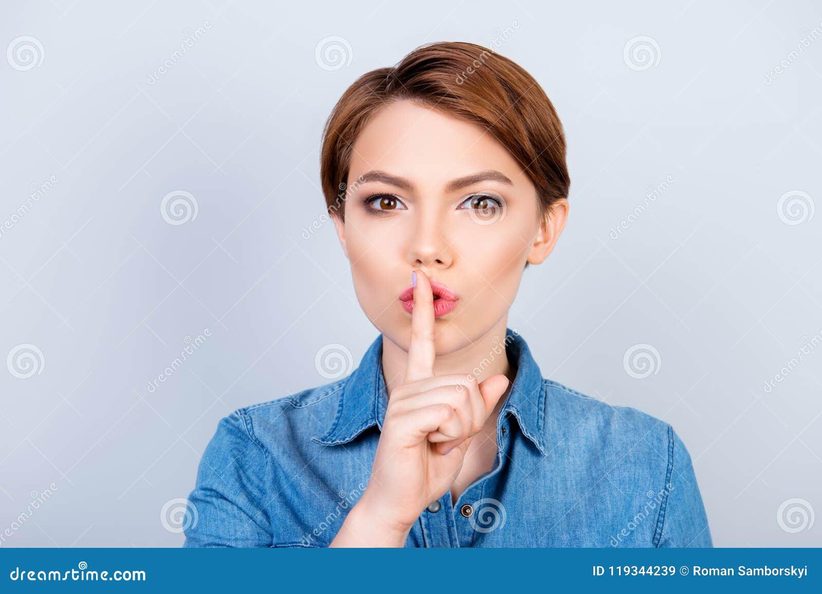 Shh! Het meisje toont iemand om stil te houden en haar secre te vertellen