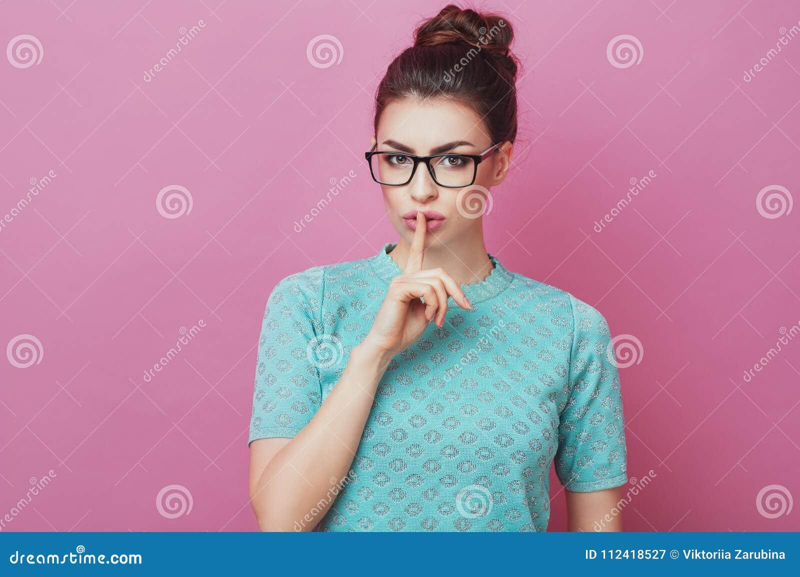 Shh! Ståenden av den nätta kvinnlign med den stilfulla hårbullen och glasögonuppehällen fingrar på kanter, visar tystnadtecknet,