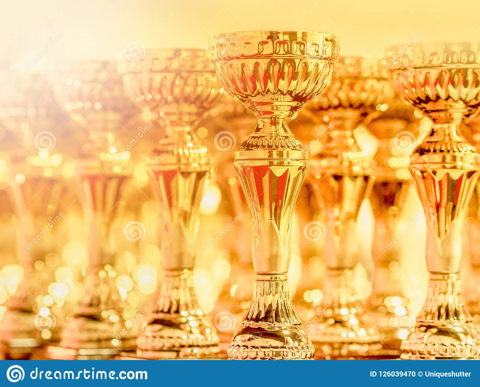 The shining trophy is the honor of the winner, Shiny Golden throphy line-up on table
