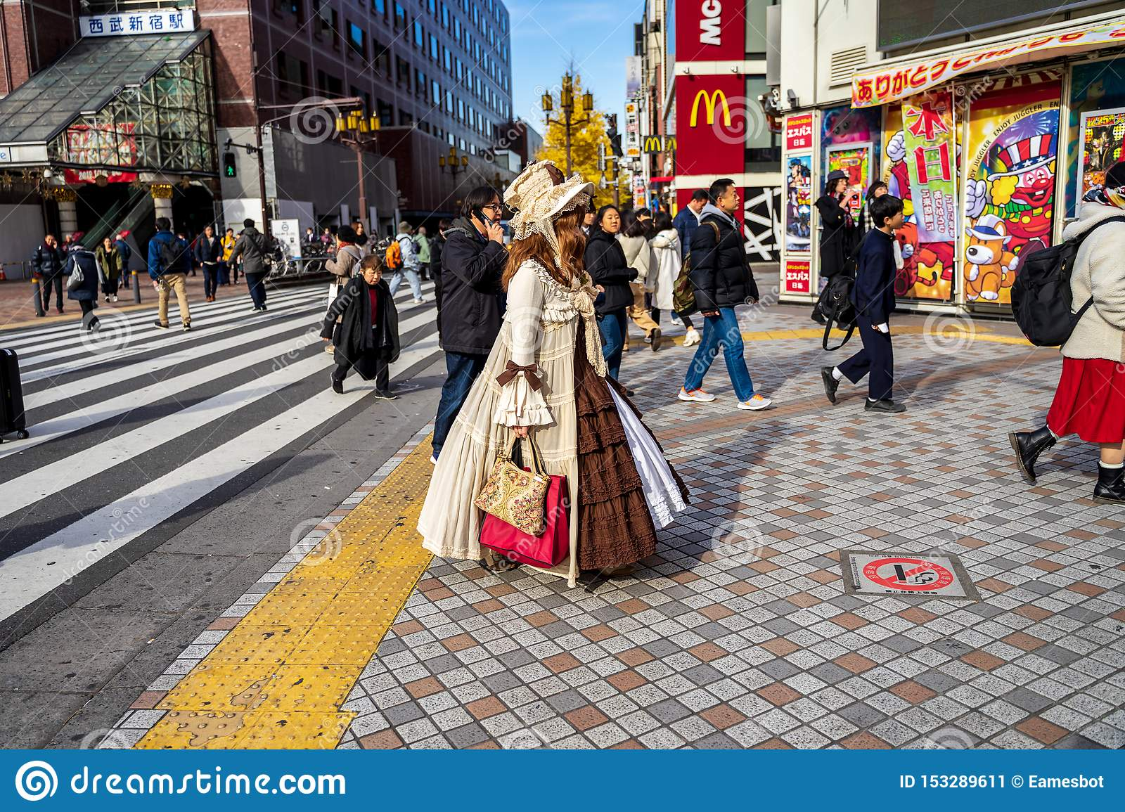 Shinjuku, Tokyo, Japan - December 26, 2018: Beautiful girl with crossplay suit waling in the crowd pedestrians people. Famous