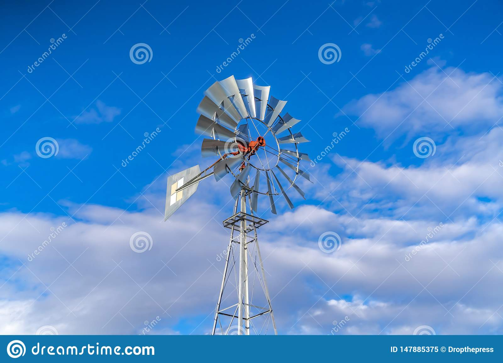 Shiny steel windpump against a vibrant blue sky with cottony clouds