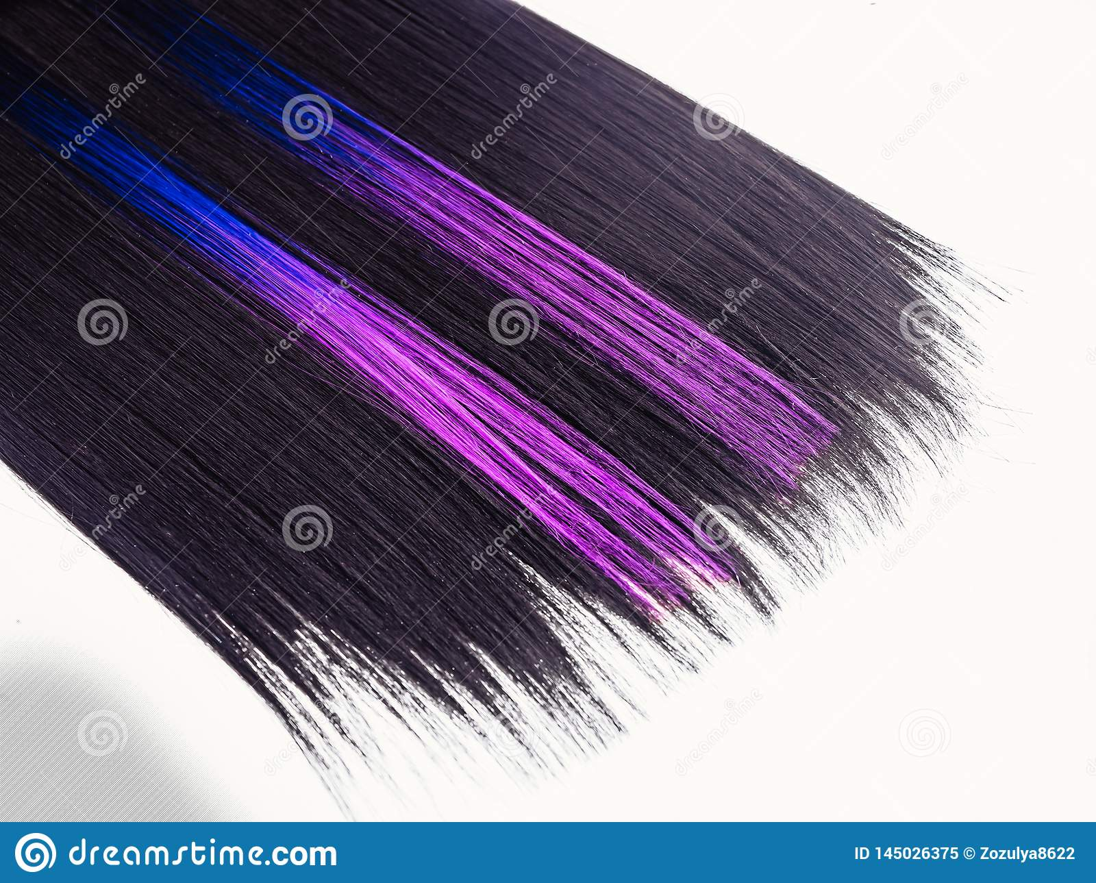 Shiny straight black hair background. Beautiful smooth brunette hair with colored purple lilac blue strands. Beauty