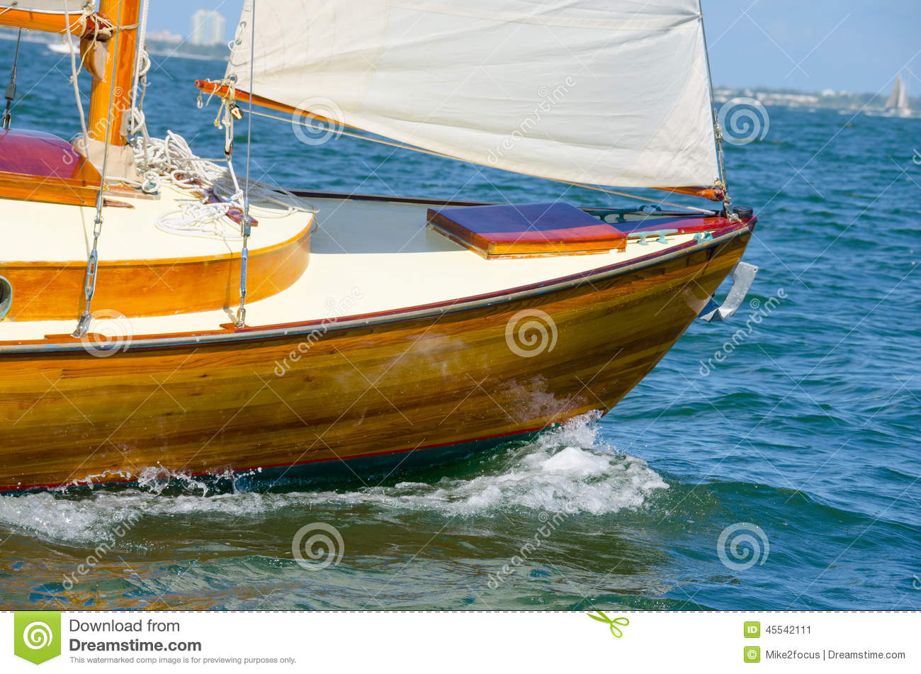 ... through blue water with refllections of the boat wake on the hull
