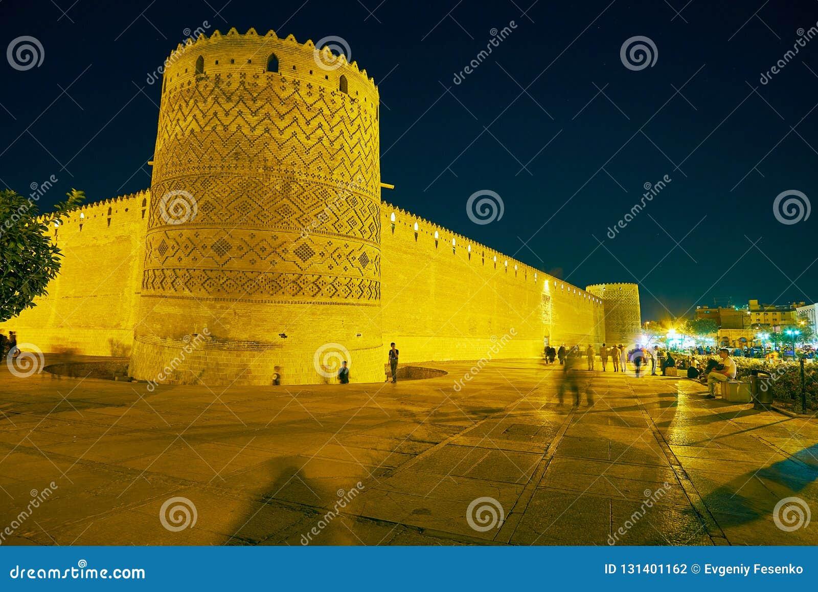 SHIRAZ, IRAN - OKTOBER 14, 2017: Geniet van middeleeuws Karim Khan Citadel in heldere die avondverlichting, door prettige tuinen