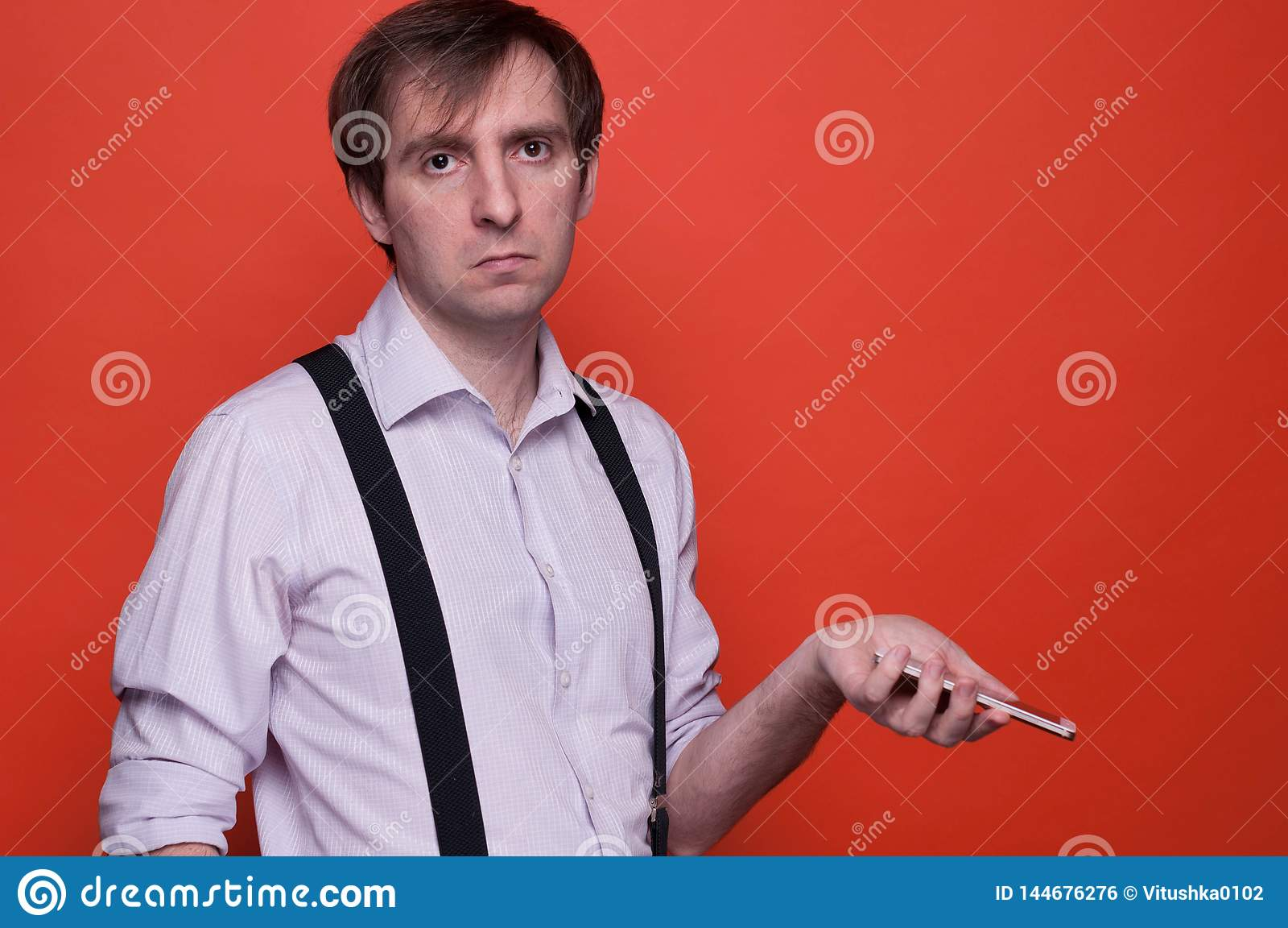 Disappointed handsome man holding smartphone on orange background