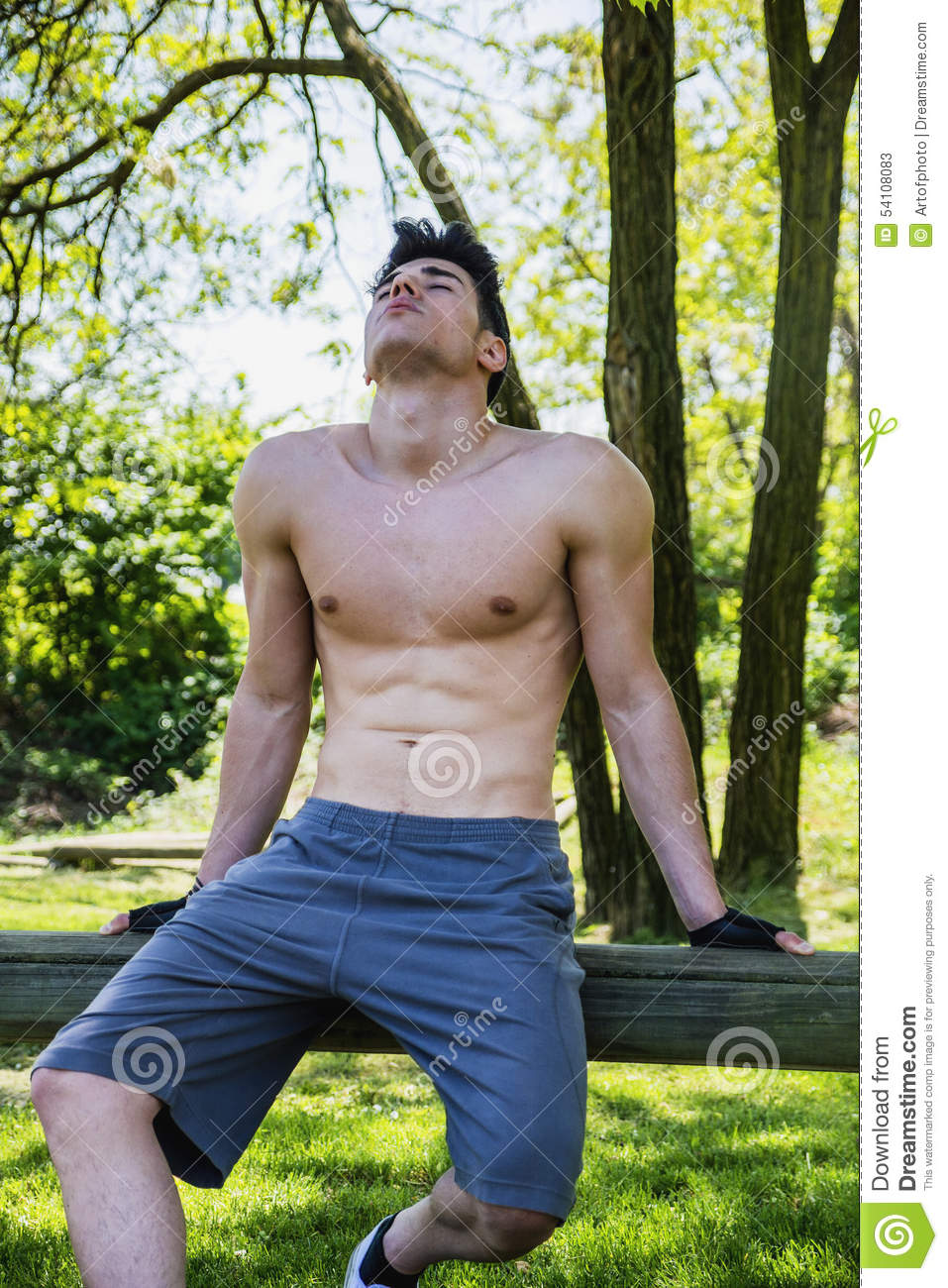 Shirtless athletic young man resting in city park