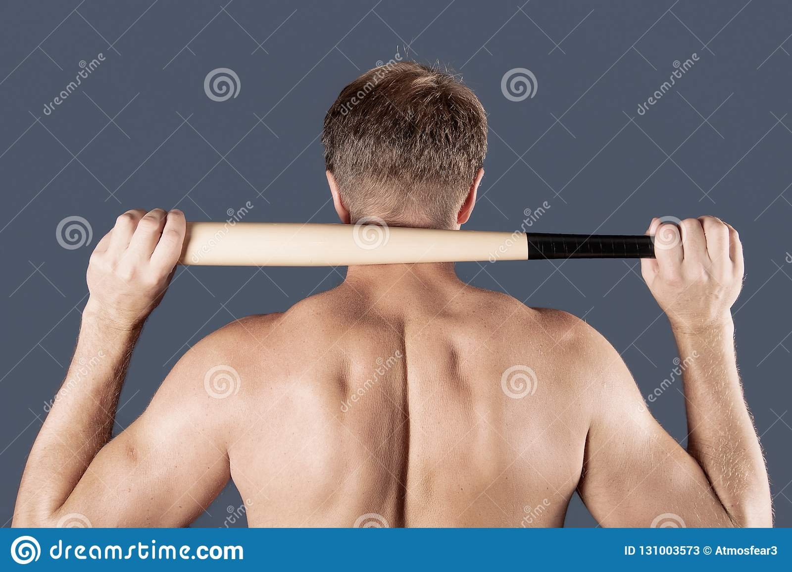Shirtless man holds on his shoulders a baseball bat over blue background
