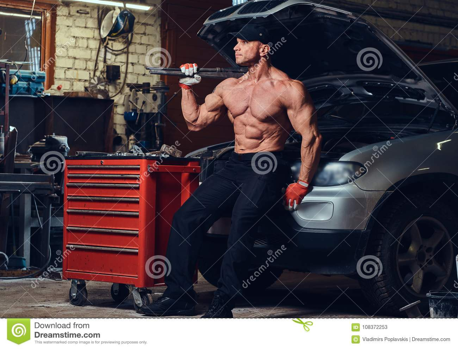 Shirtless mekaniker i ett garage