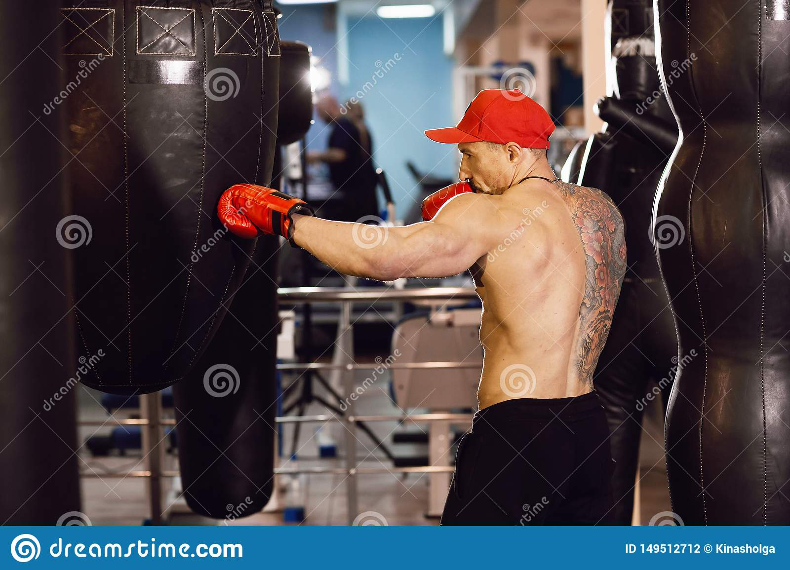 Shirtless muscular boxer with punching bag in gym. A man with a tattoo in red boxing gloves