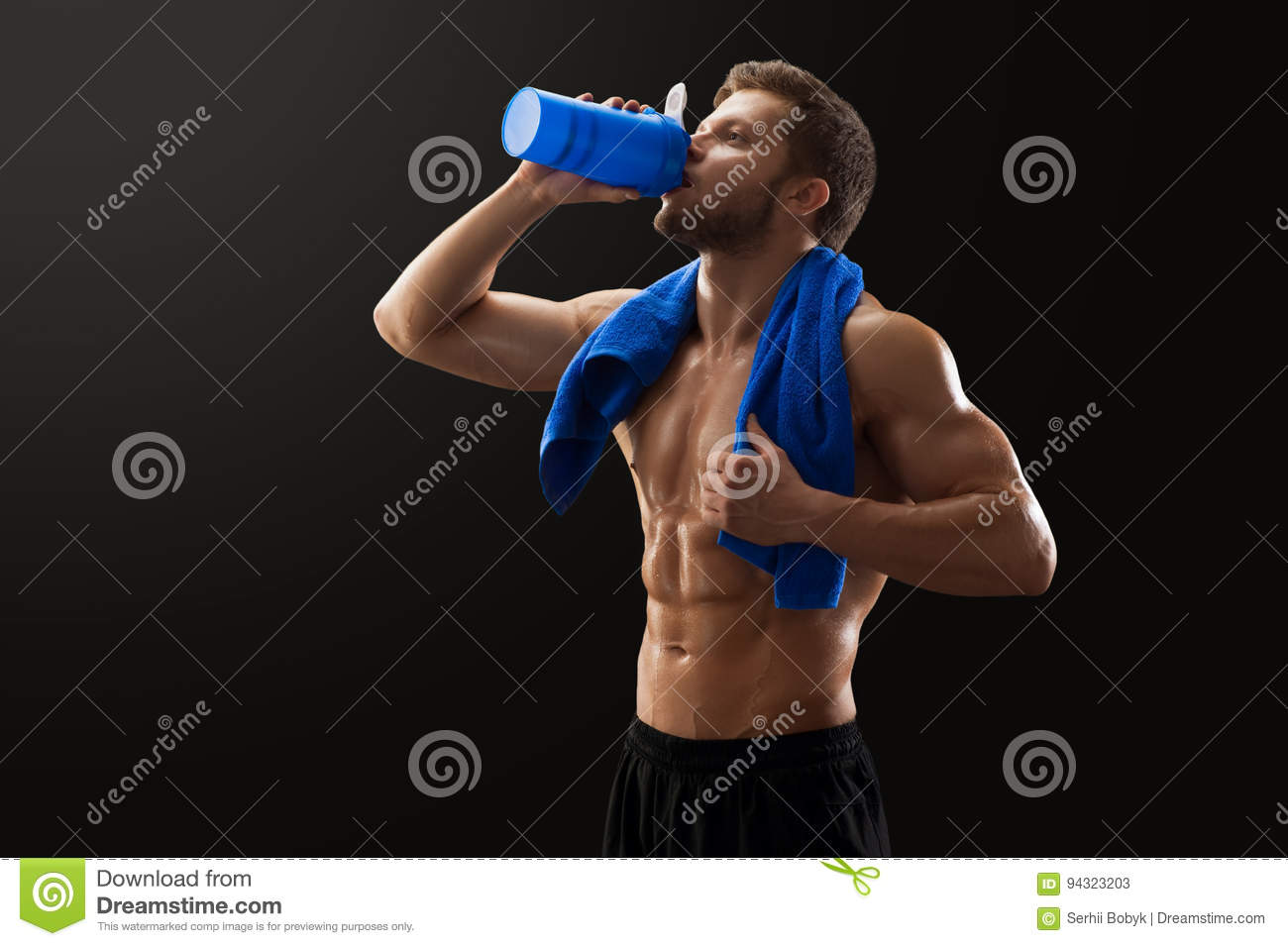 Muscular young man with a towel drinking water after exercising at the gym  bodybuilding crossfit training sport health motivation determination  athletics. 3569a78d62