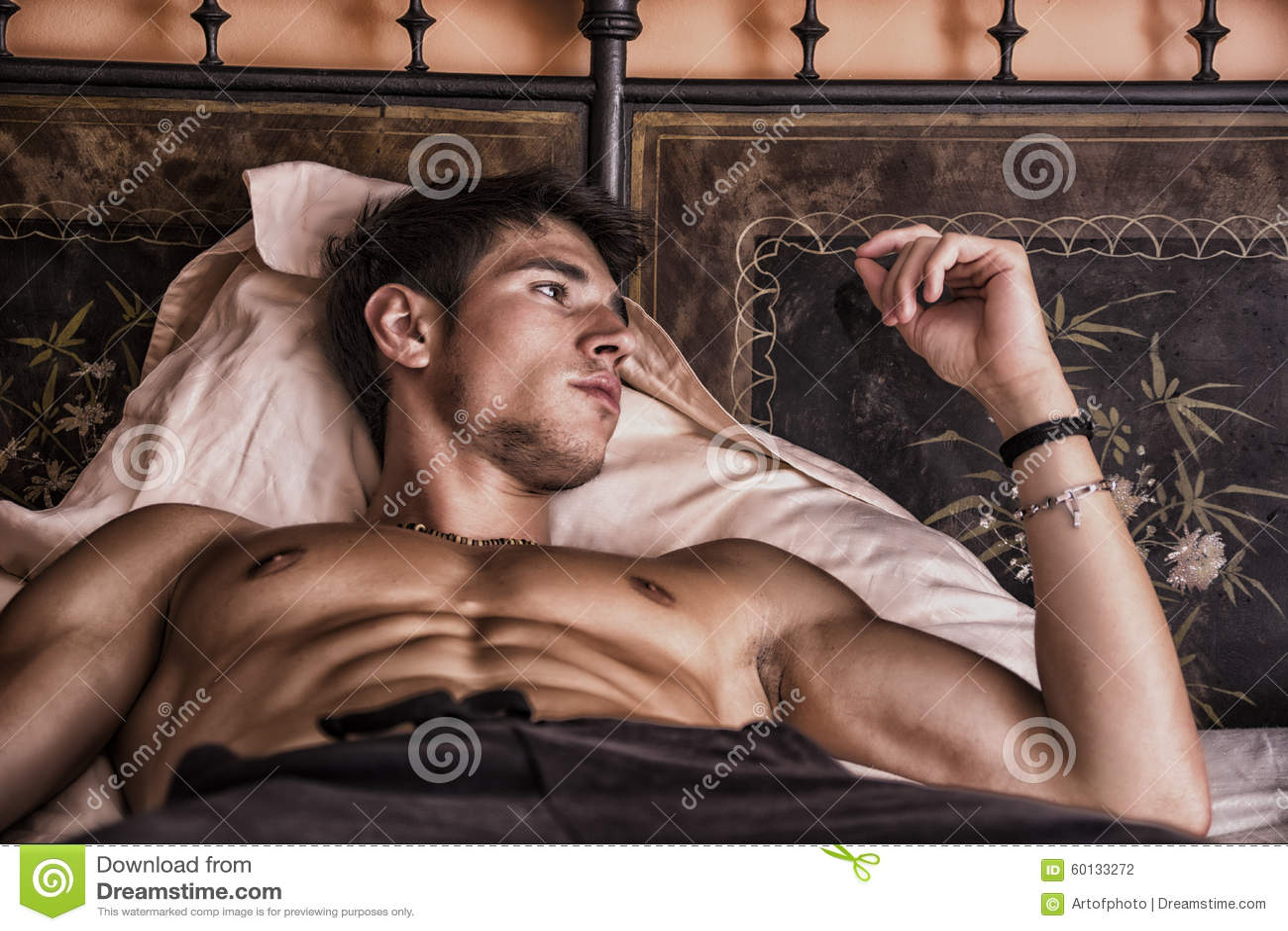 Shirtless sexig manlig modell som bara ligger på hans säng
