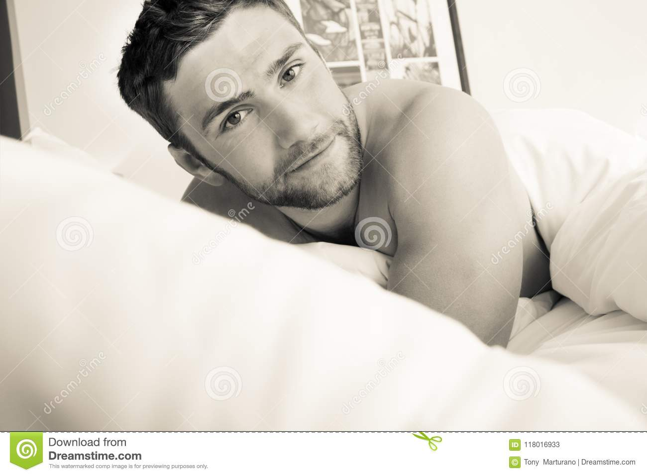 Shirtless hunky man with beard lies naked in bed