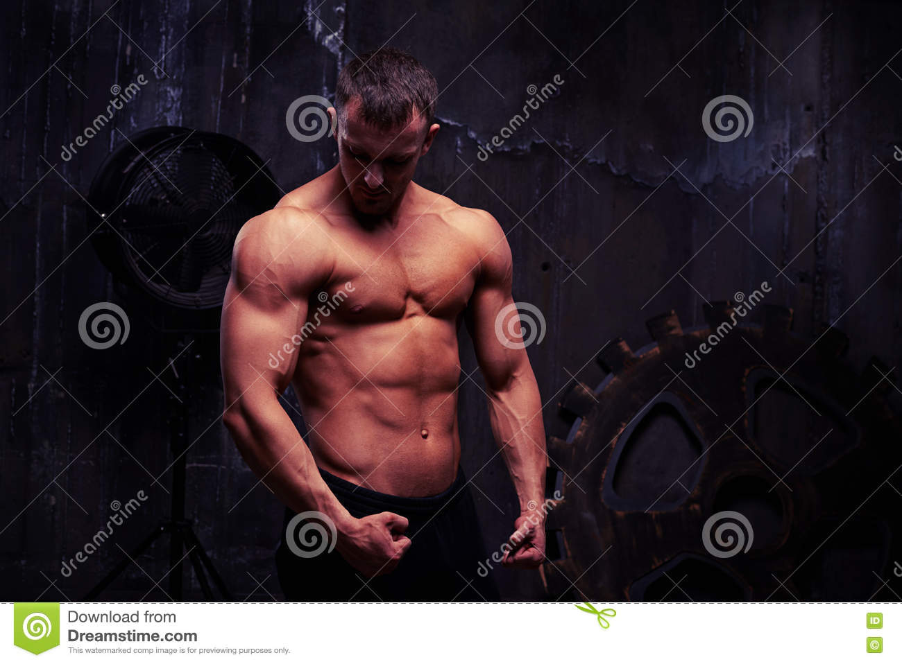 Shirtless male is posing against the wall with big rusty ge