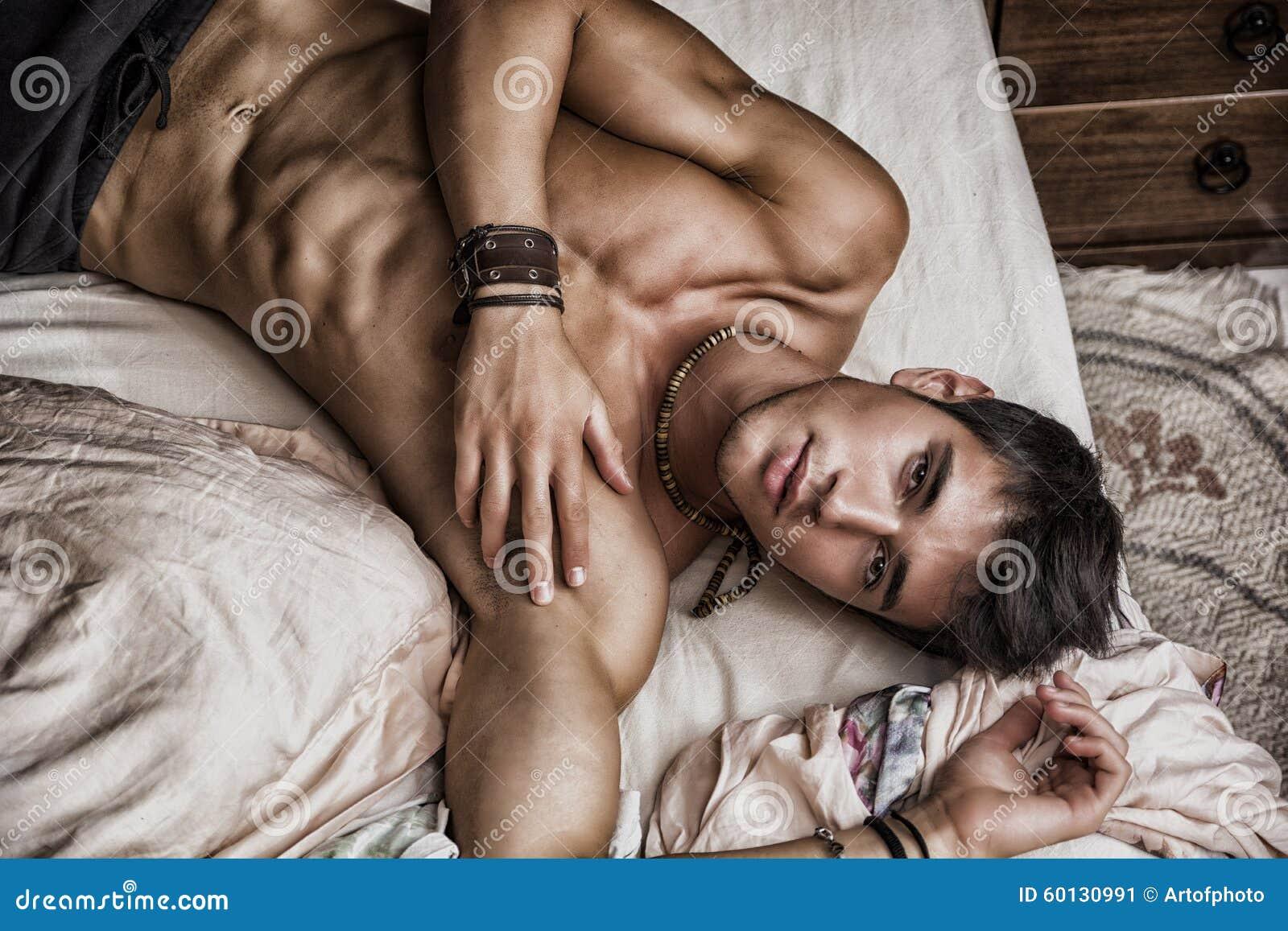 Shirtless sexy mannelijk model die alleen op zijn bed liggen