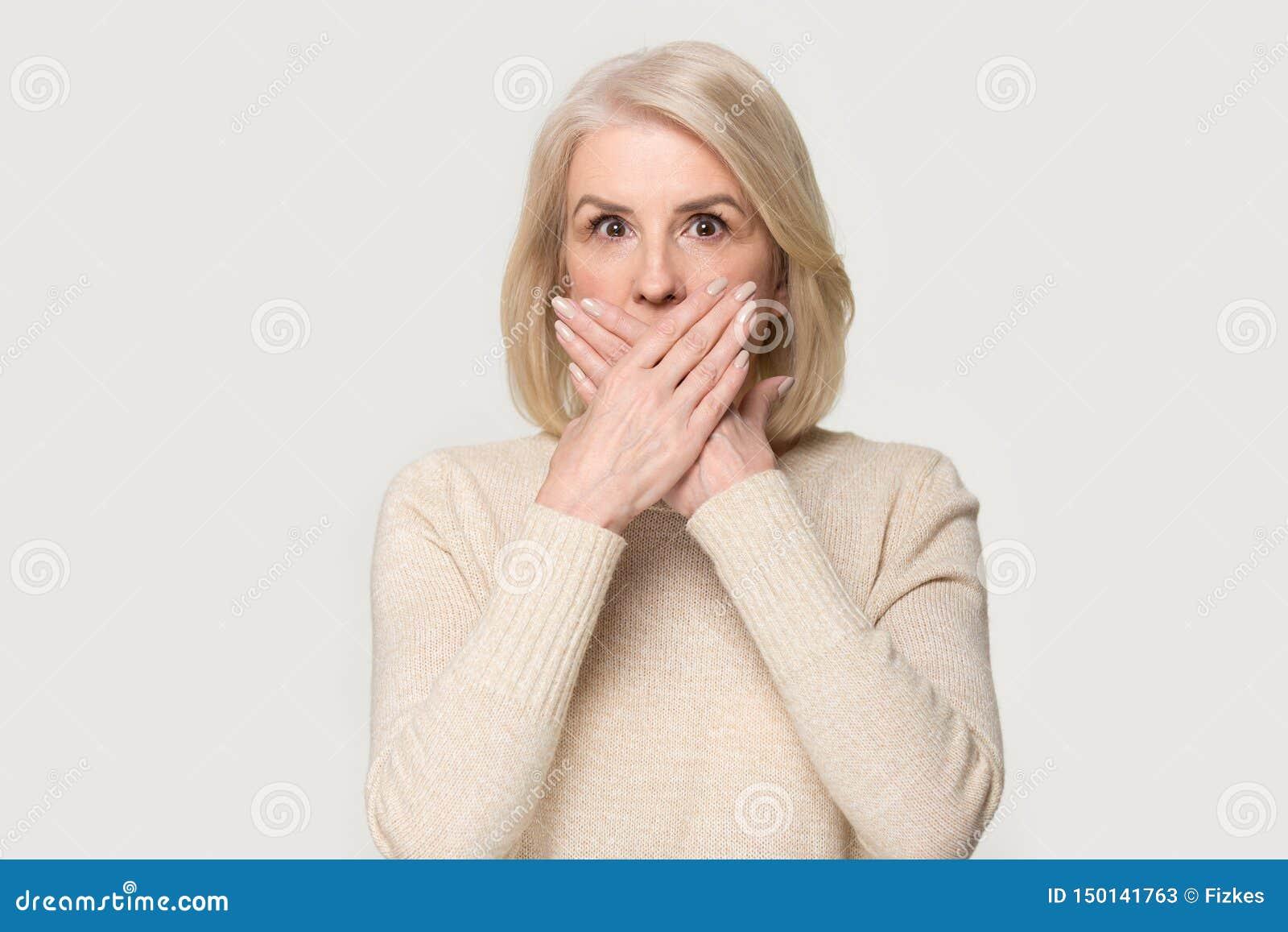 Shocked åldrades den kvinnliga täckande munnen med händer känner sig förskräckt