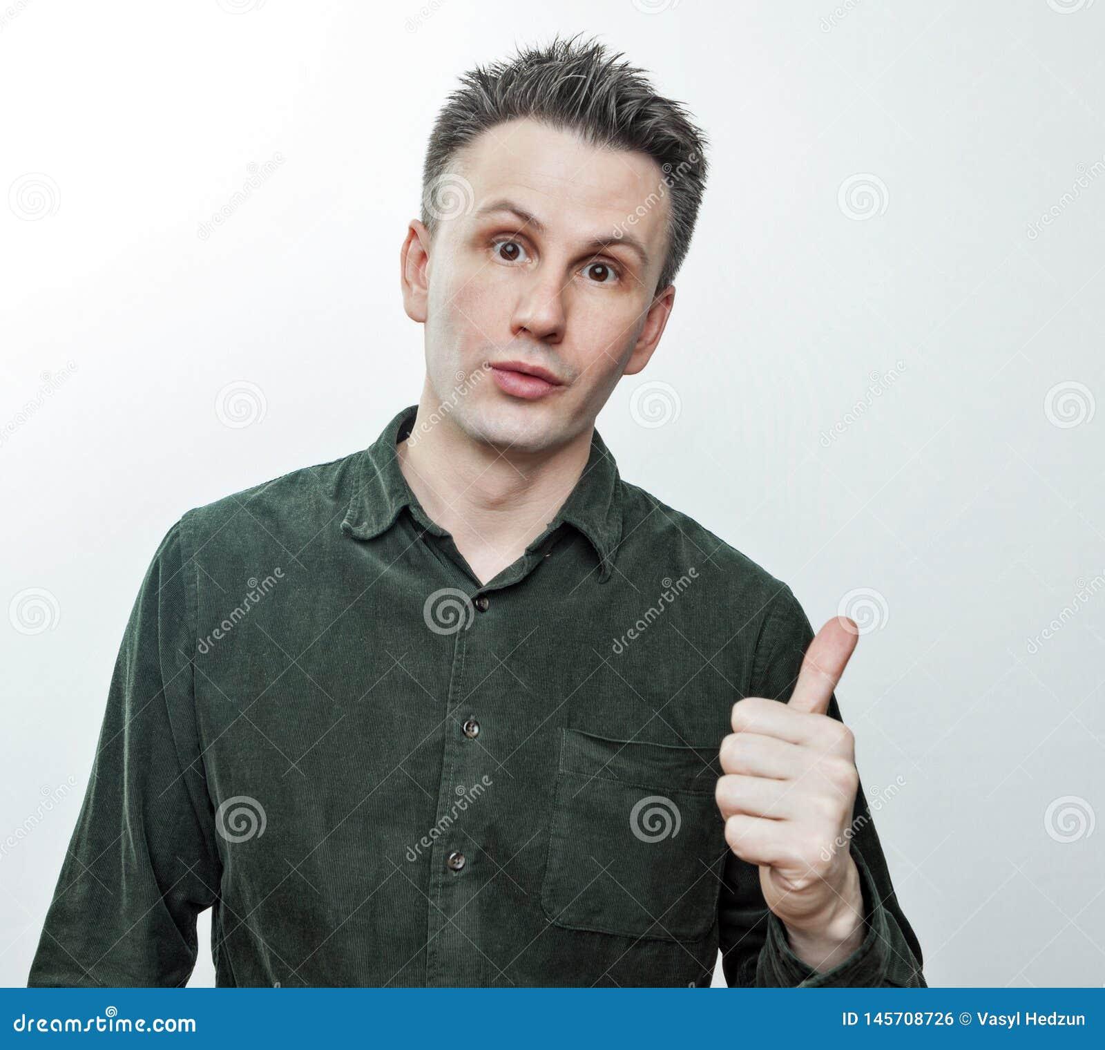 Shocked оглушил молодой человека указывая палец в сторону на удивленное представление пустой рекламы космоса экземпляра невероятн