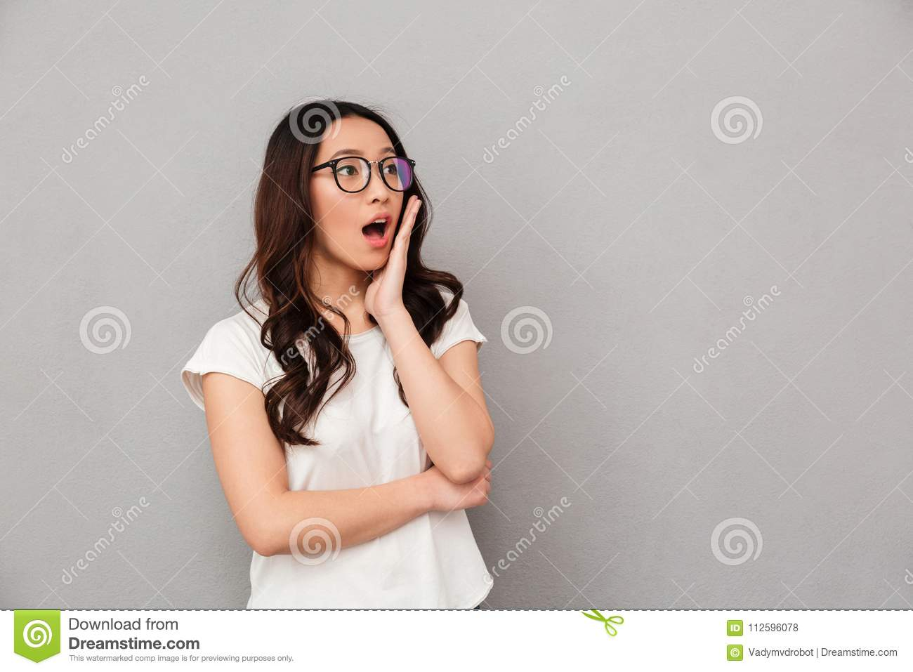 Shocked asian woman in t-shirt and eyeglasses holding her cheek