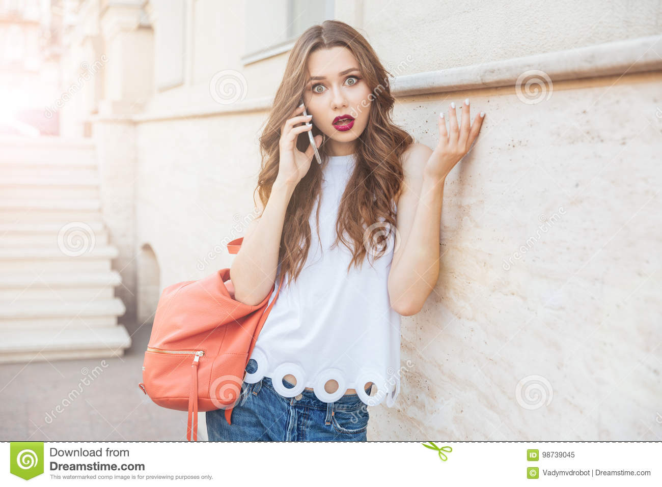 Shocked beautiful young woman holding her smartphone outdoors