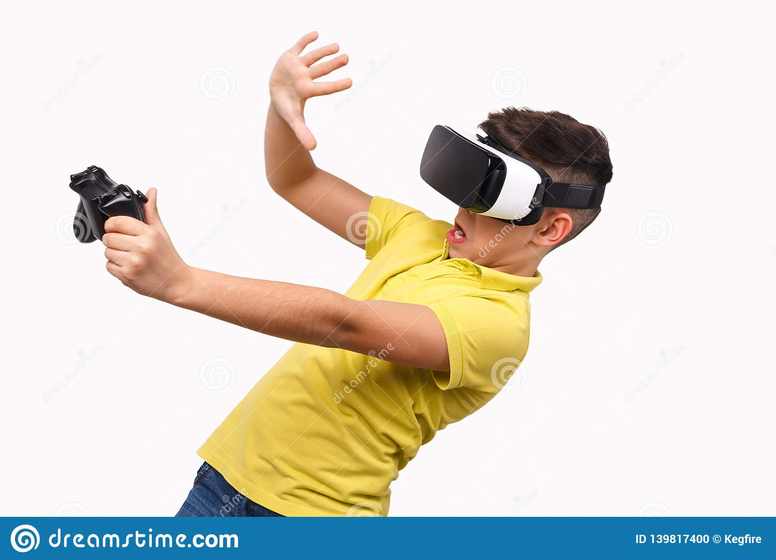 bcd650f6ffe Funny boy in VR headset holding controller and leaning back with shocked  grimace while standing on white background