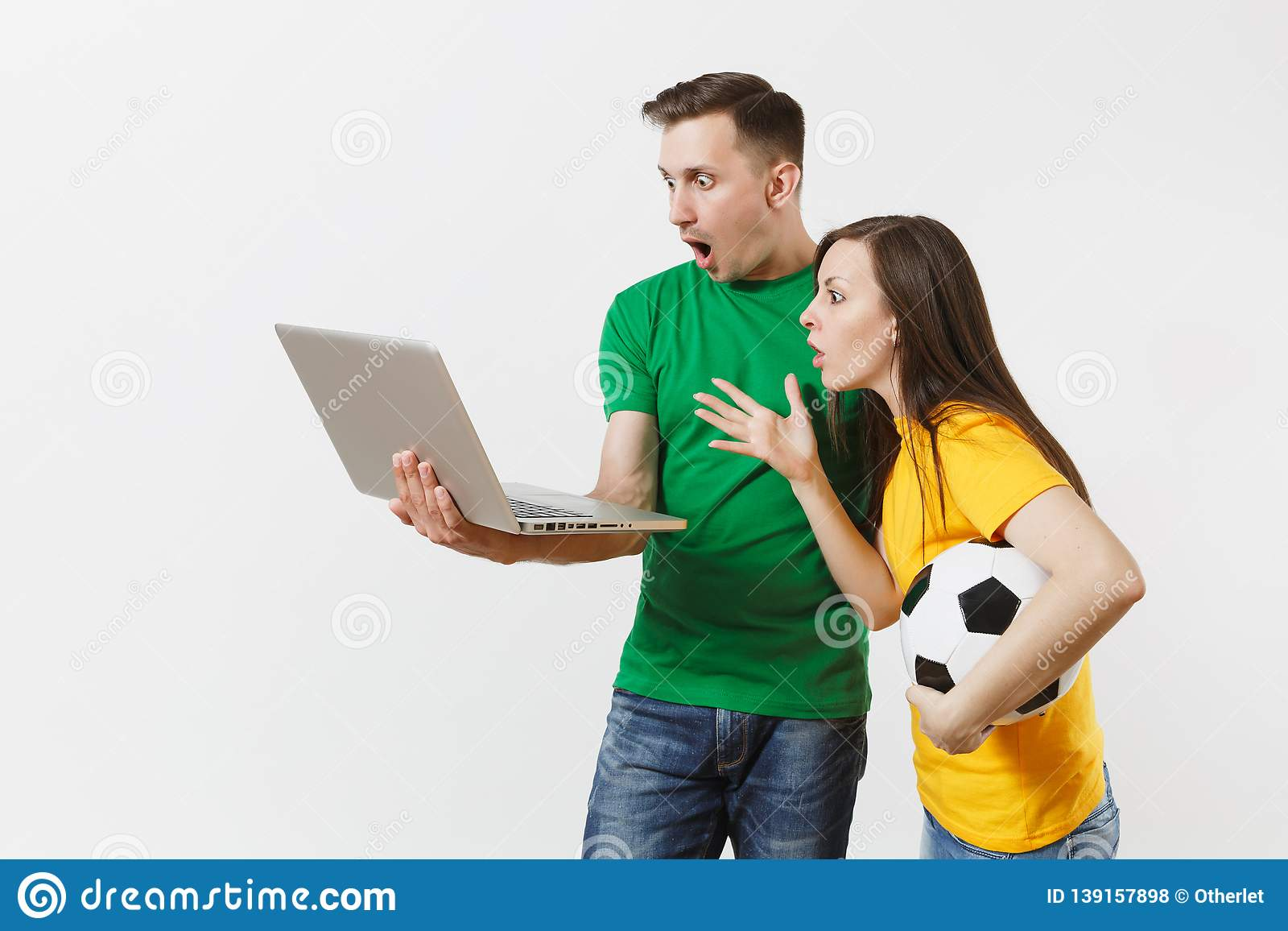Shocked couple woman man, football fans in yellow green t-shirt cheer up support team with soccer ball, watching game on
