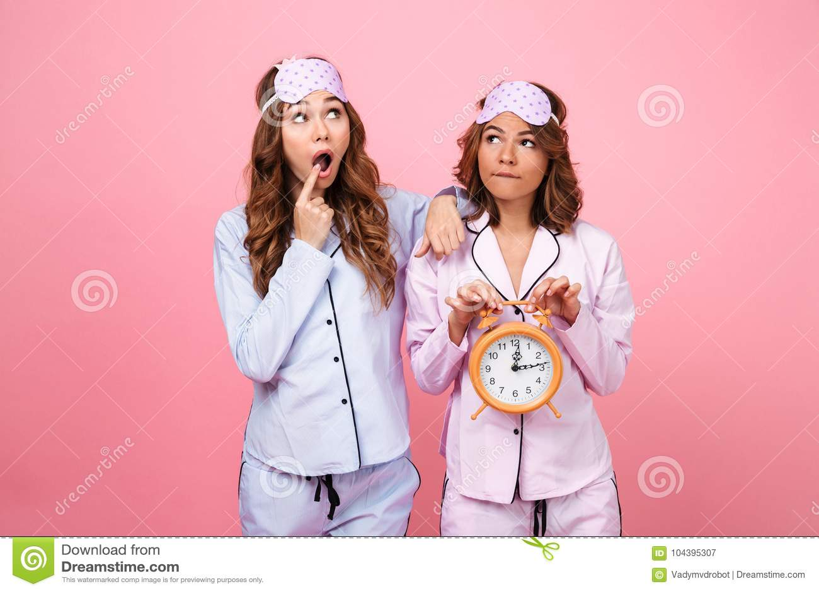 Shocked friends women in pajamas holding alarm clock