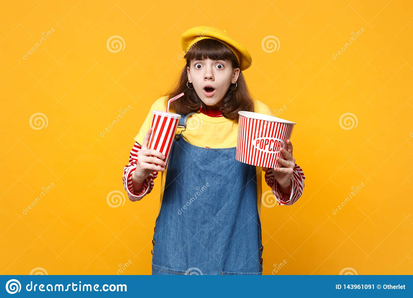 Shocked girl teenager in french beret, denim sundress hold plastic cup of cola or soda, bucket of popcorn isolated on