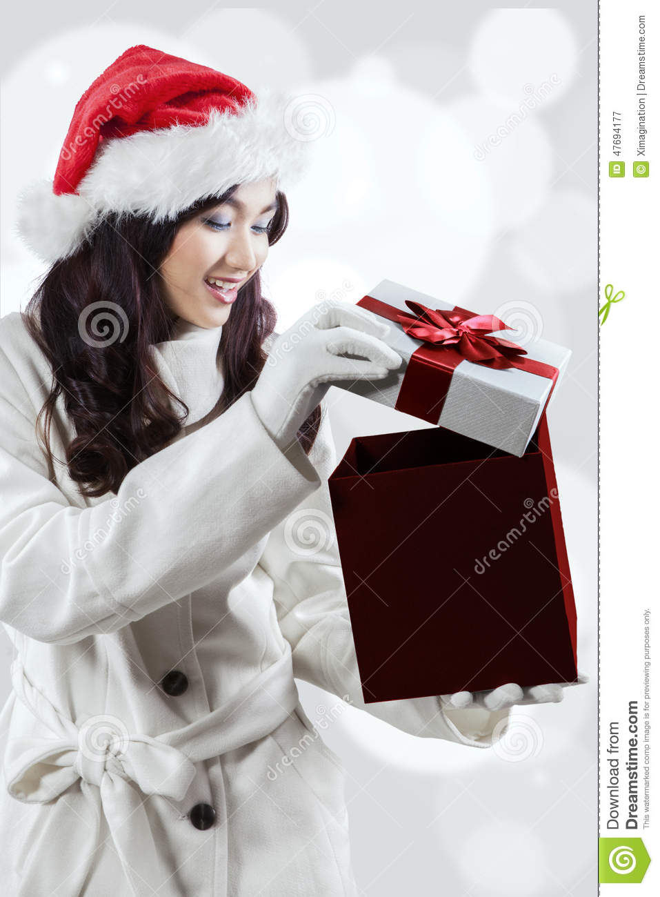 Shocked girl in winter clothes opening a gift