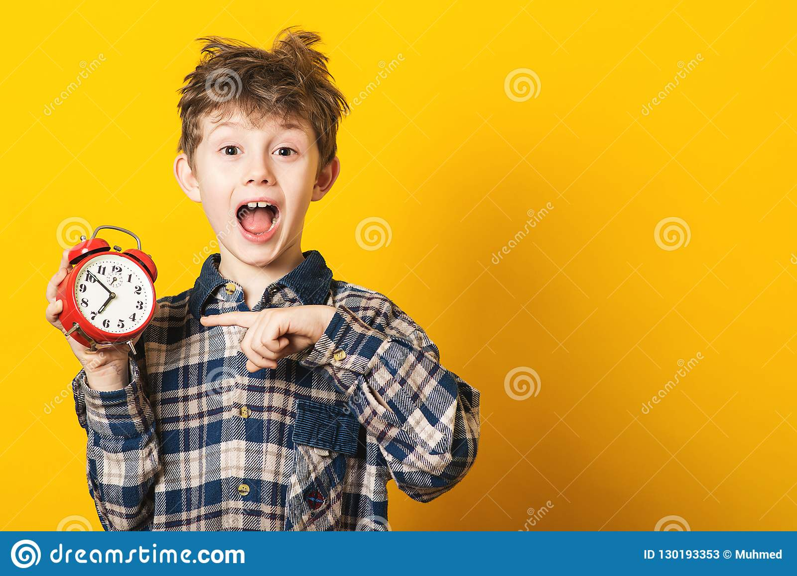Shocked kid boy holding clock alarm, copy space. Kid isolated over yellow background. Time for school. Little student overslept. T