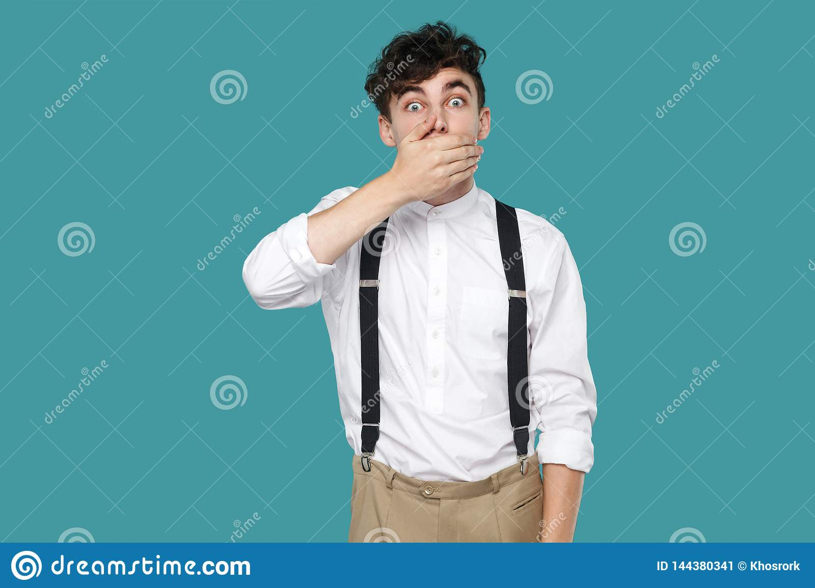 Shocked man covering his mouth, looking at camera with big eyes