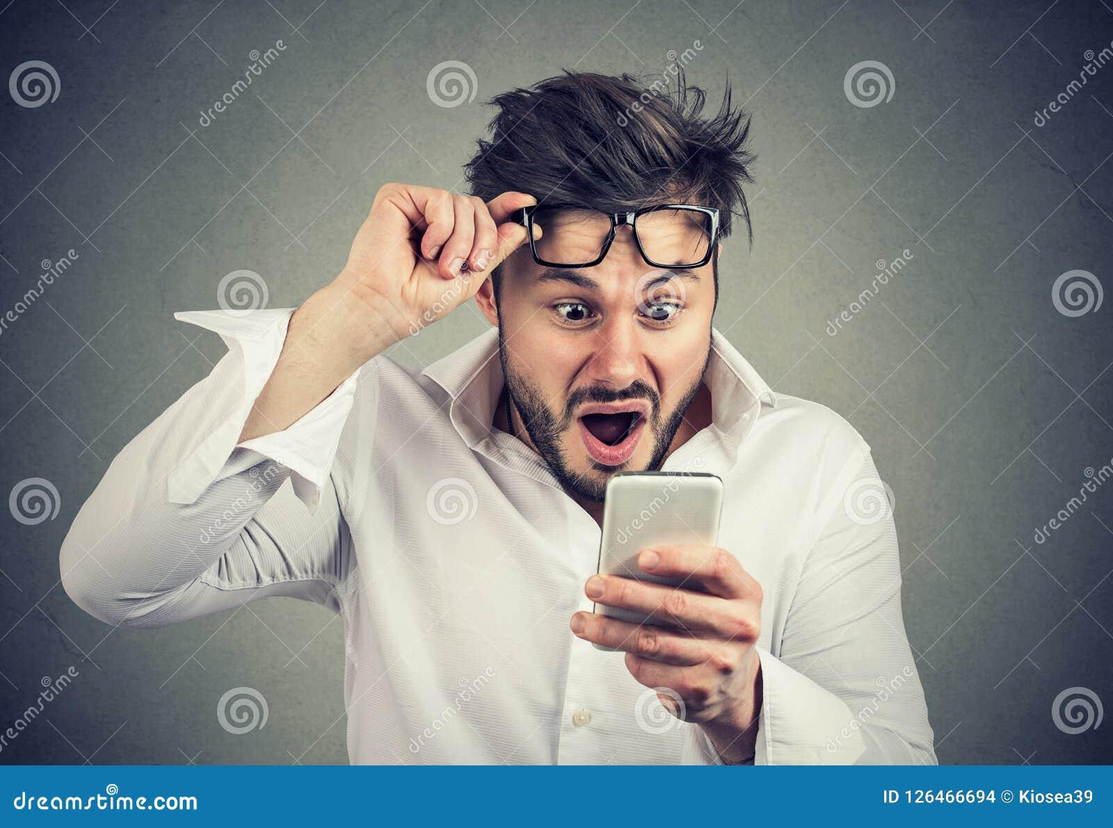 Shocked man reading news on smartphone