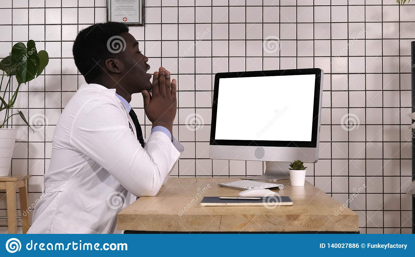 Shocked medical doctor looking on the screen of computer. White Display.