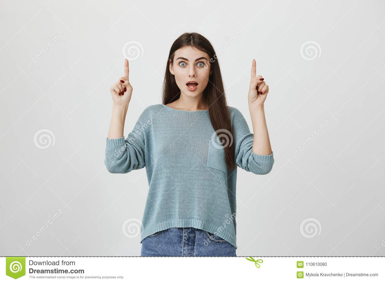 Shocked And Surprised Young Model Pointing Up With Index