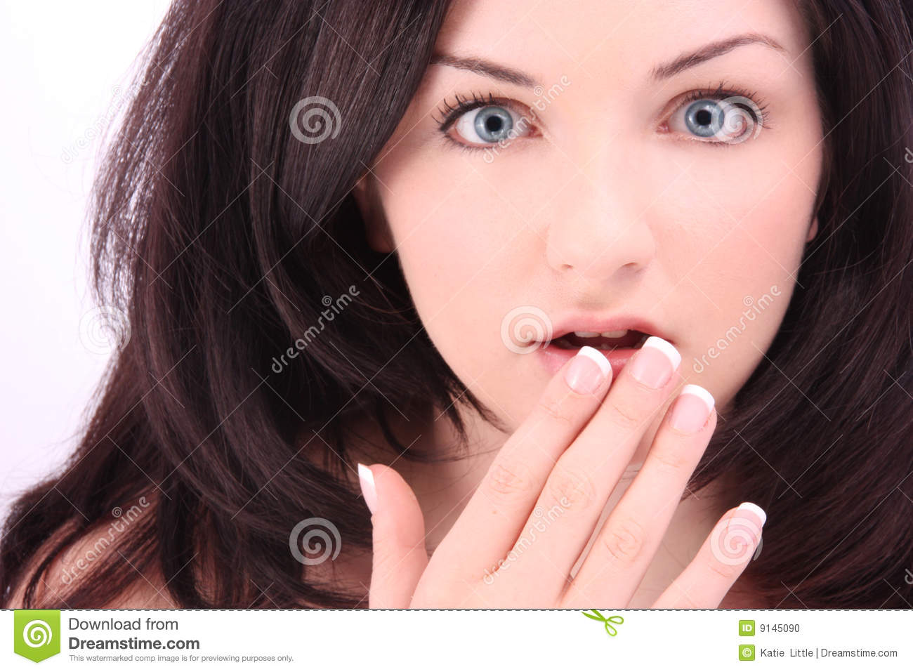 young beautiful woman with a suprised expression in front of a white ...