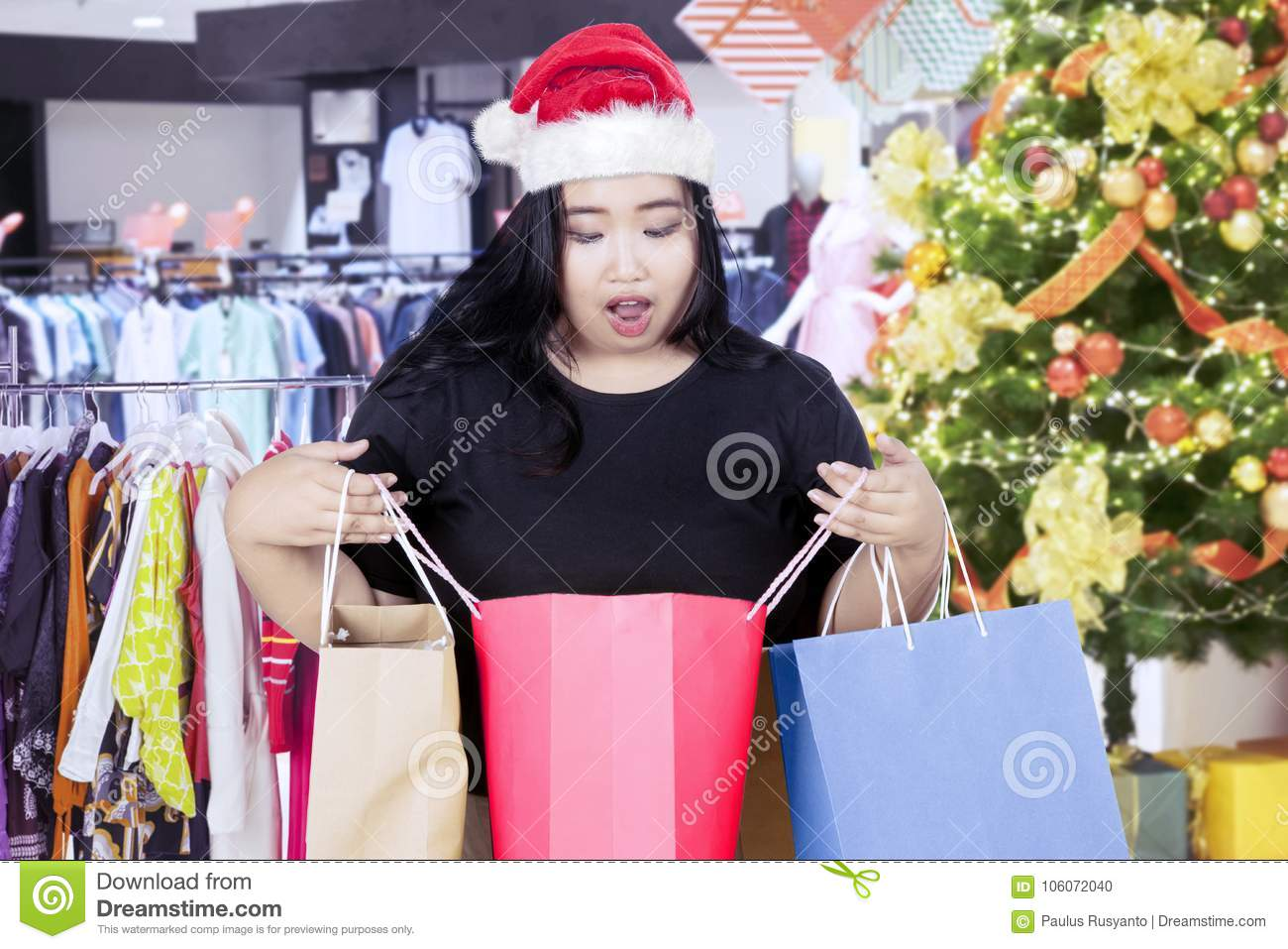Shocked woman opening a shopping bag