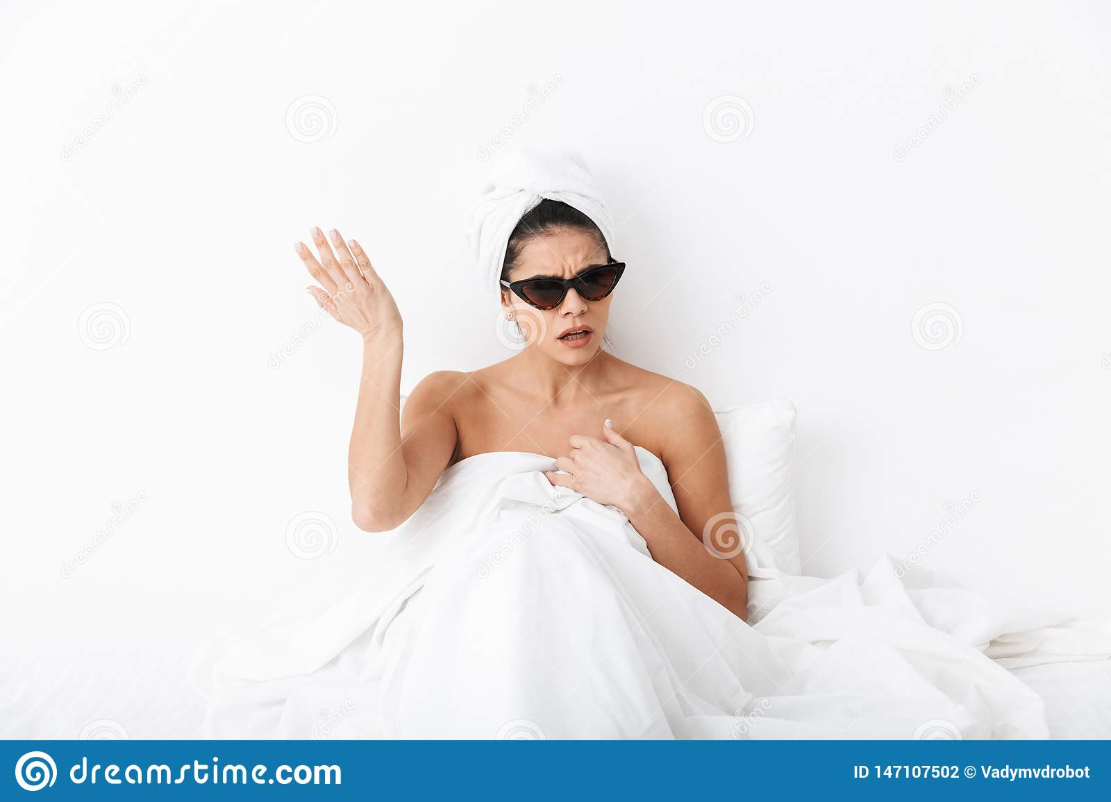 Shocked woman with towel on head lies in bed under blanket isolated over white wall background wearing sunglasses
