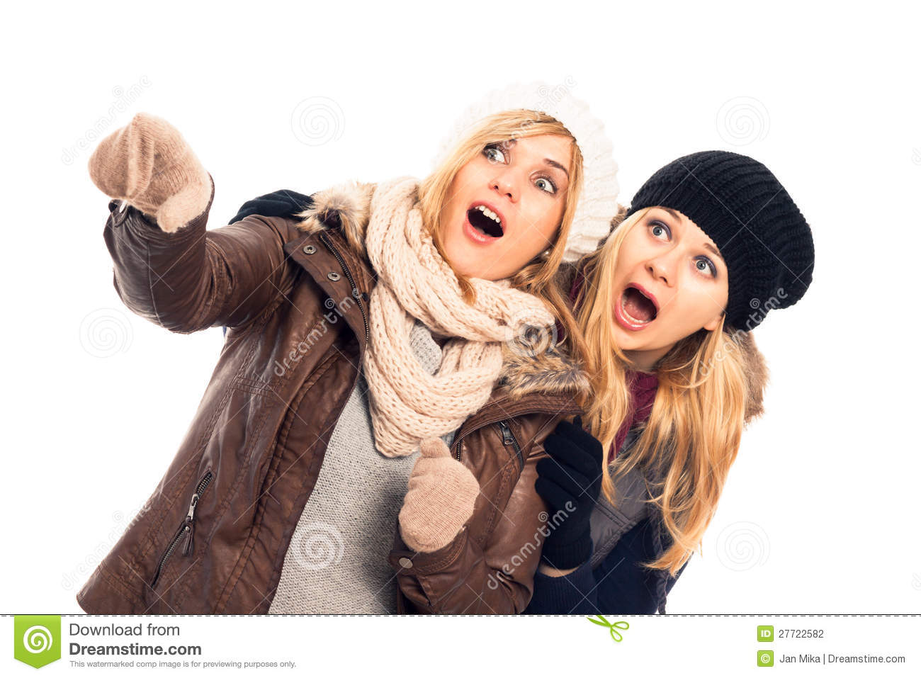 Two young shocked women in winter clothes pointing, isolated on white ...