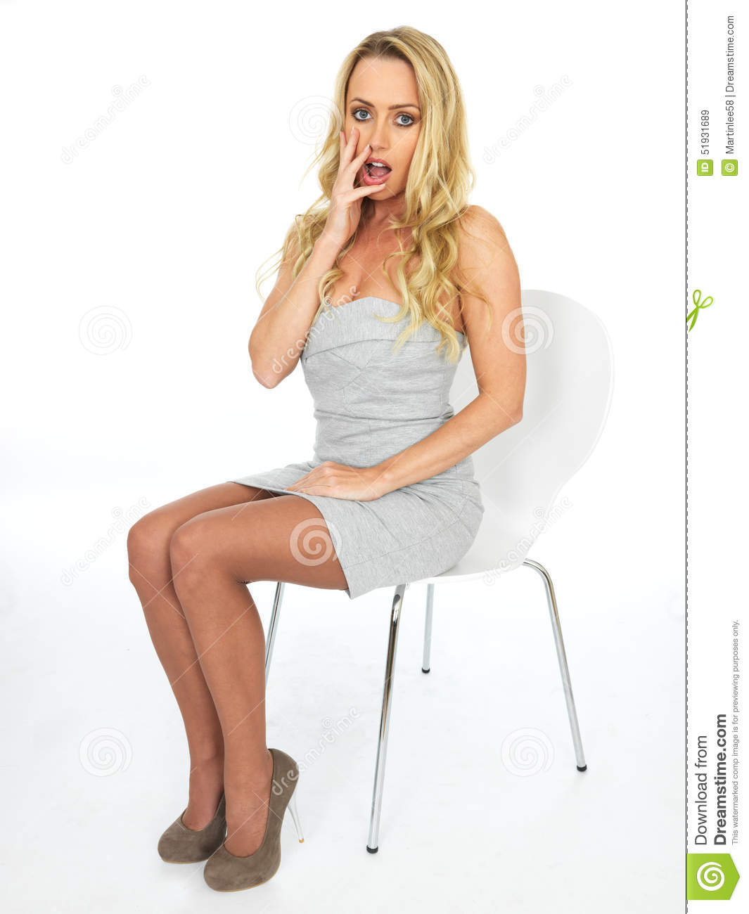 f569265cb9c Shocked Attractive Worried Young Business Woman, wearing a short mini dress,  sitting in a chair, looking at the camera. Shot against a white background.