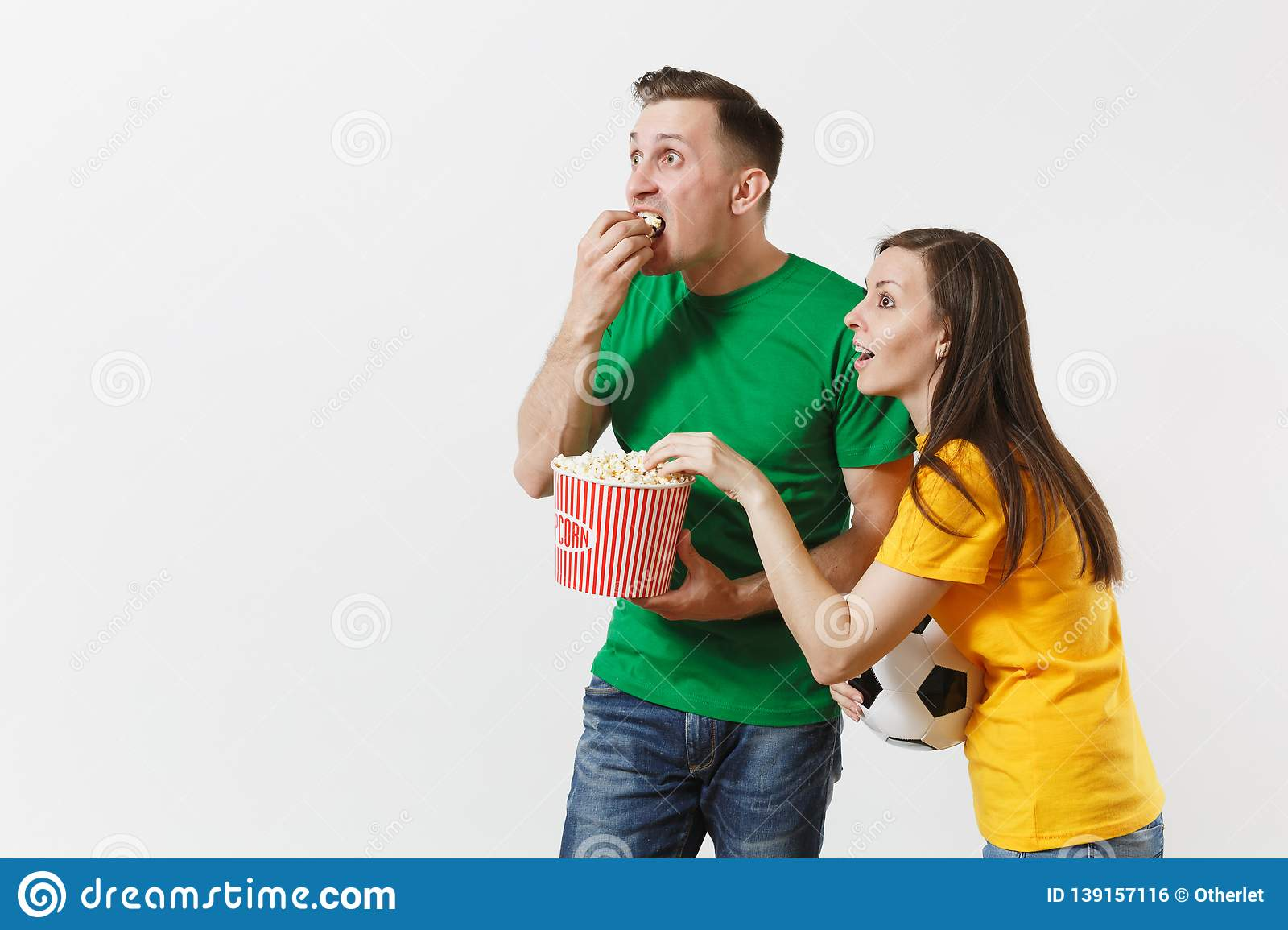 Shocked young couple, woman, man, football fans in yellow green t-shirt cheer up support team with soccer ball bucket of