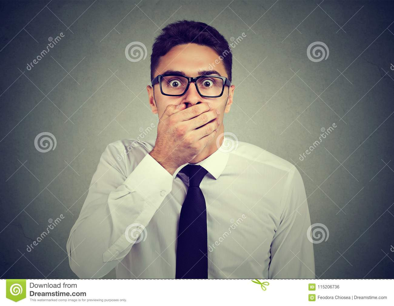 Shocked young man covering his mouth with hand