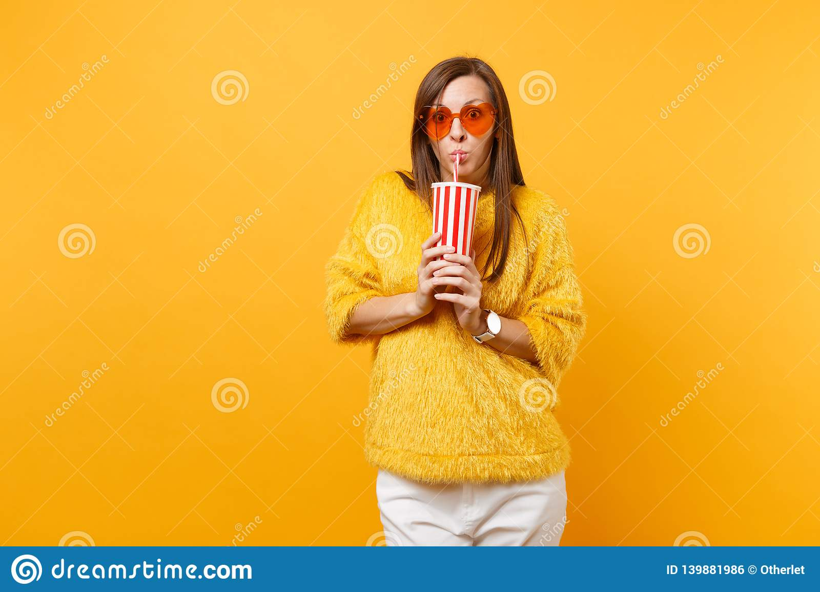 Shocked young woman in fur sweater and heart orange glasses drinking cola or soda from plastic cup isolated on bright