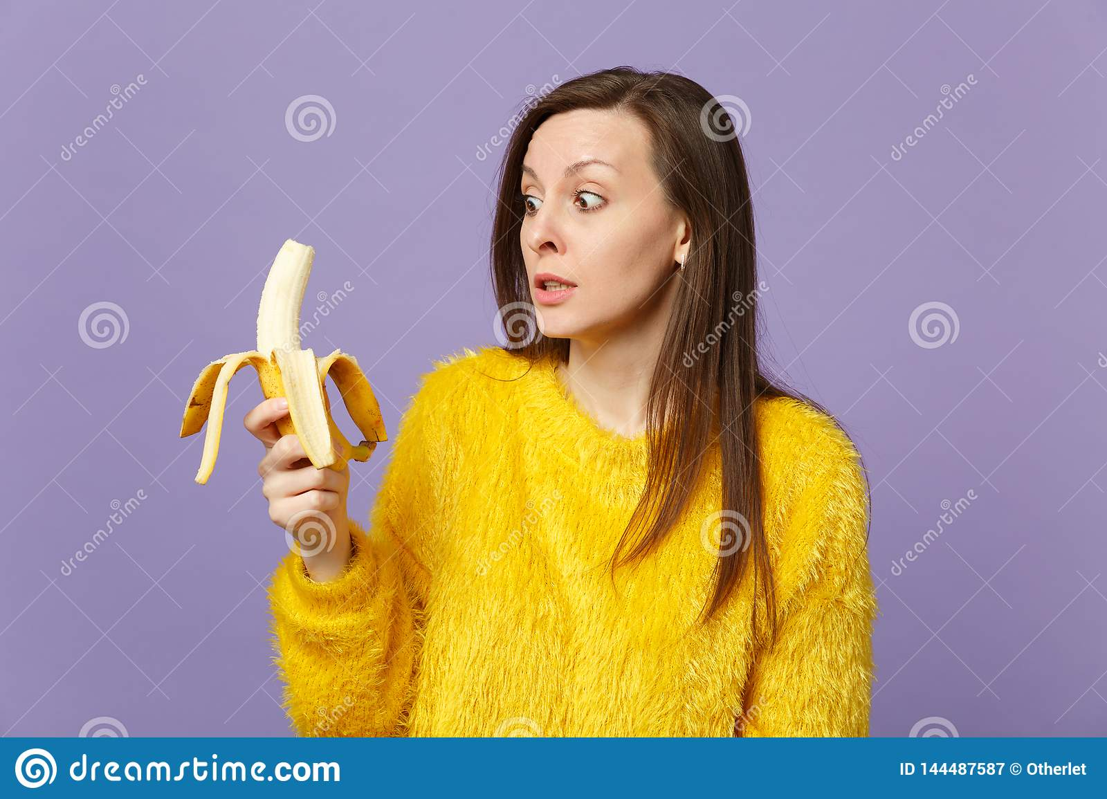 Shocked young woman in fur sweater holding in hand, looking on fresh ripe banana fruit isolated on violet pastel wall