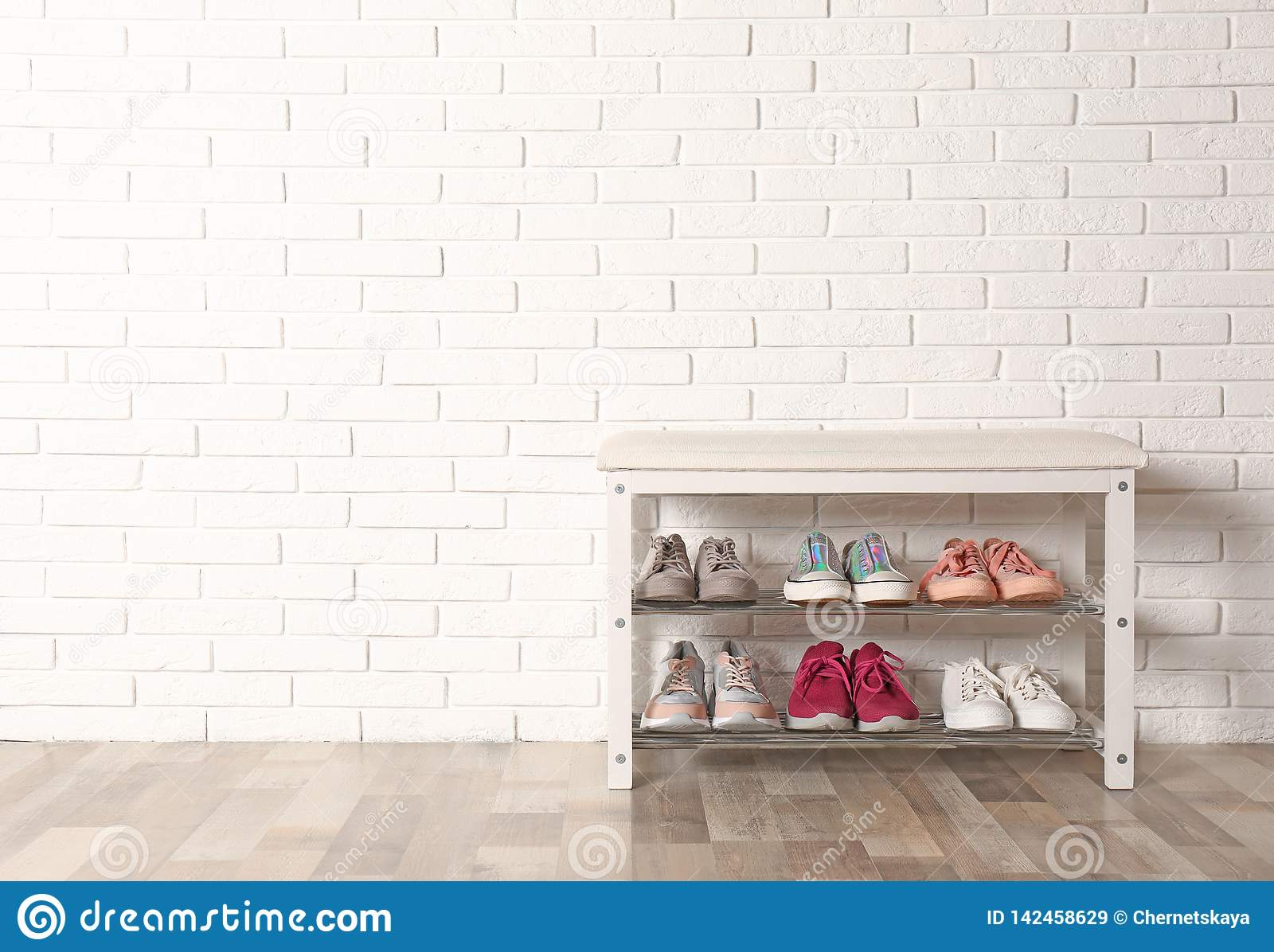 Shoe storage bench with different sneakers near wall, space for text