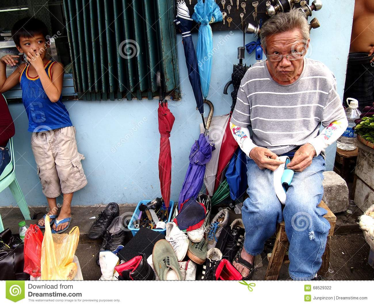 A shoemaker repairs a shoe for a customer along a street in Antipolo City, Philippines