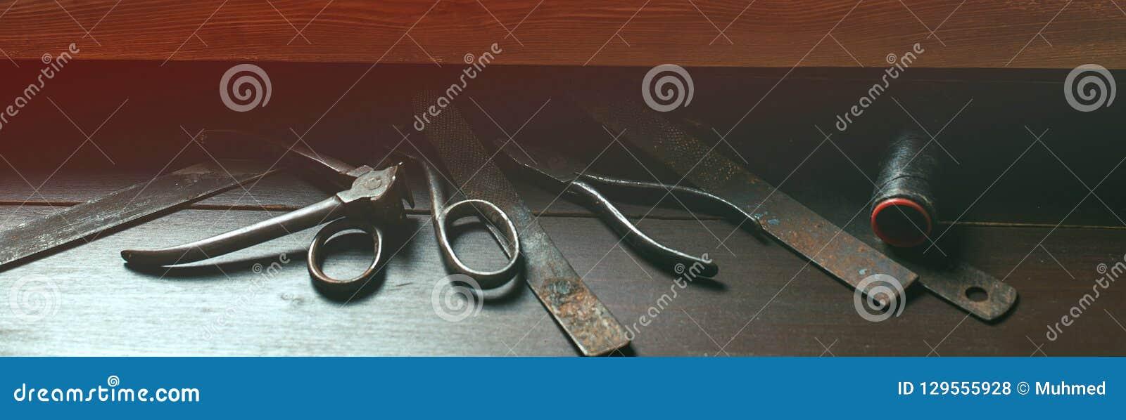 Shoemaker`s work desk. Old tools on wooden table. Shoemaker`s shop. Instruments at cobbler workplace. Vintage style. Shoes maker