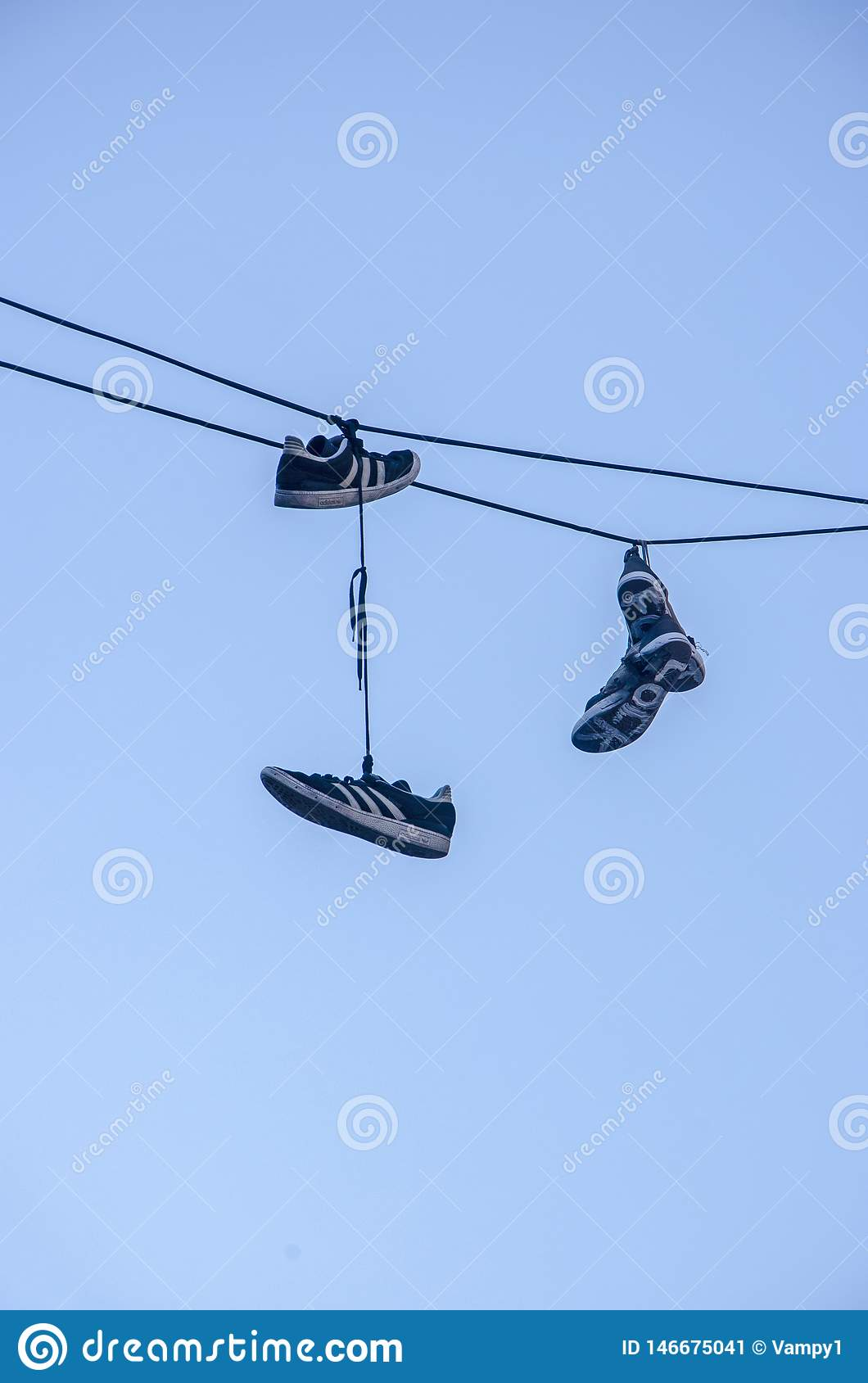 Shoes Hanging From Electric Power Wires. Shoe Laces And