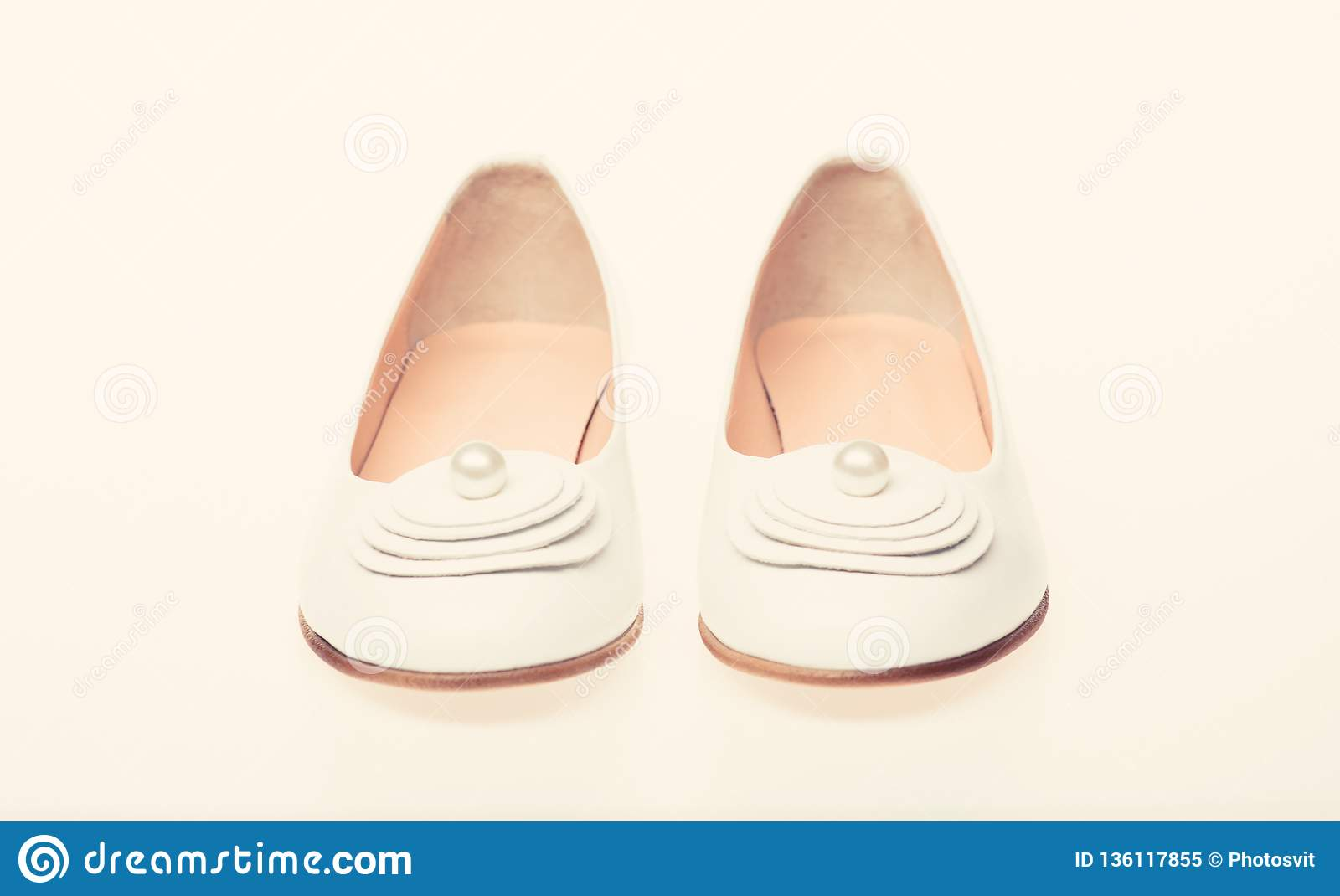 825f8fa8a Shoes made out of white leather on white background, isolated. Footwear for  women on flat sole with pearl bead as decor. Minimalism concept.