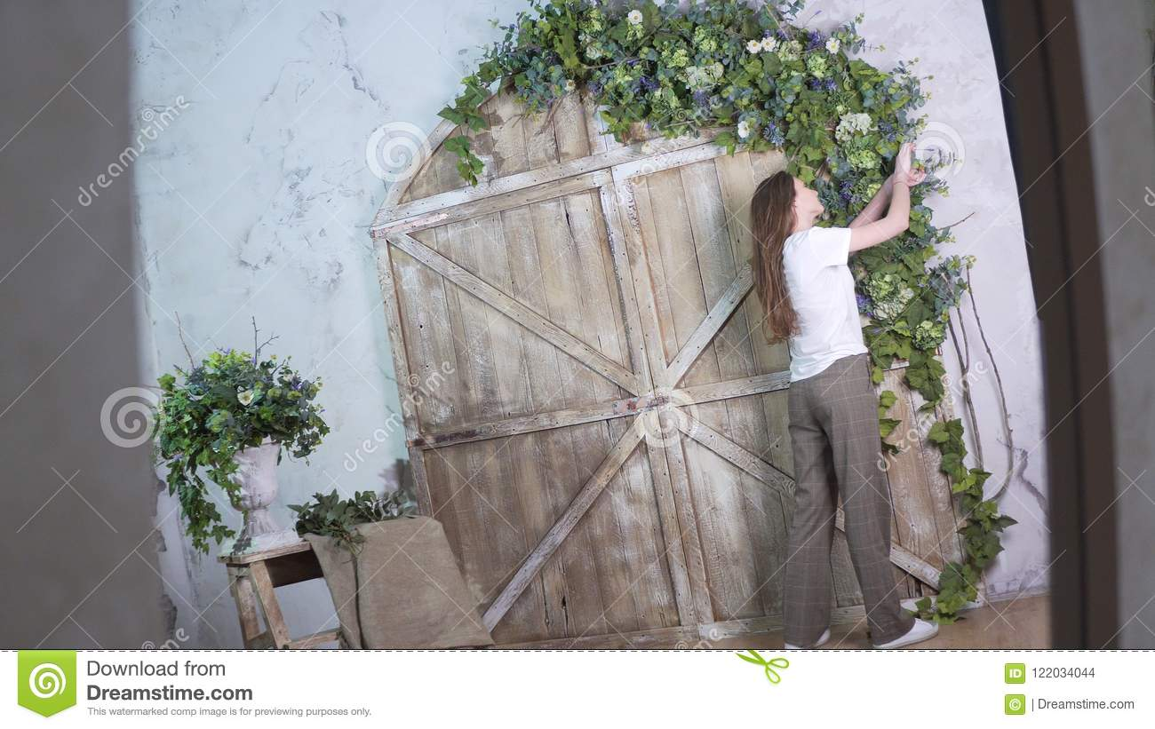 Shoot in reflection, stylish girl florist decorates a beautiful wooden photo zone with flowers
